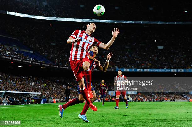 Alexis Sanchez of FC Barcelona duels for the ball with Filipe Luis of Atletico de Madrid during the Spanish Super Cup second leg match between FC...