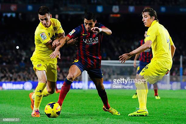 Alexis Sanchez of FC Barcelona duels for the ball with Hernan Perez and Tomas Pina of Villarreal CF of Villarreal during the La Liga match between FC...