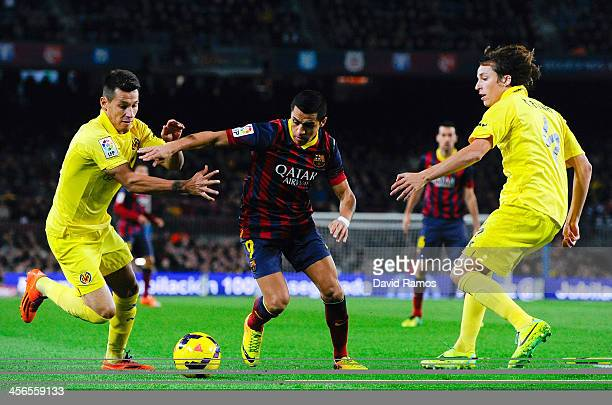 Alexis Sanchez of FC Barcelona duels for the ball with Hernan Perez and Tomas Pina of Villarreal CF during the La Liga match between FC Barcelona and...