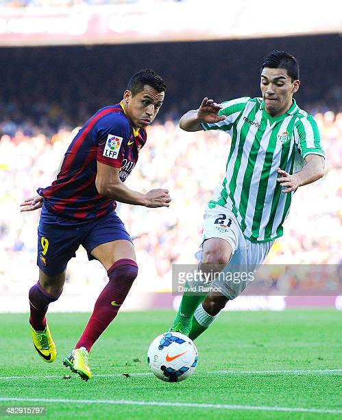 Alexis Sanchez of FC Barcelona duels for the ball with Lorenzo Reyes of Real Betis Balompie during the La Liga match between FC Barcelona and Real...