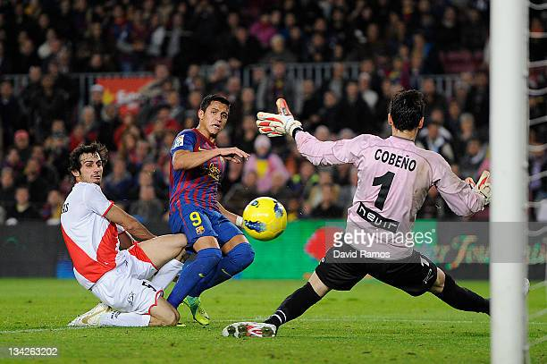 Alexis Sanchez of FC Barcelona scores his team's second goal under a challenge by David Cobeno of Rayo Vallecano and Alejandro Arribas of Rayo...