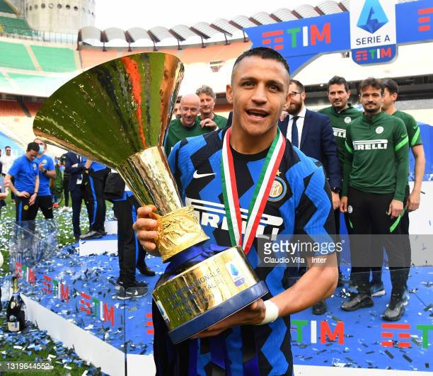 """Alexis Sanchez of FC Internazionale poses with the trophy for the victory of """"scudetto"""" at the end of the last Serie A match between FC..."""