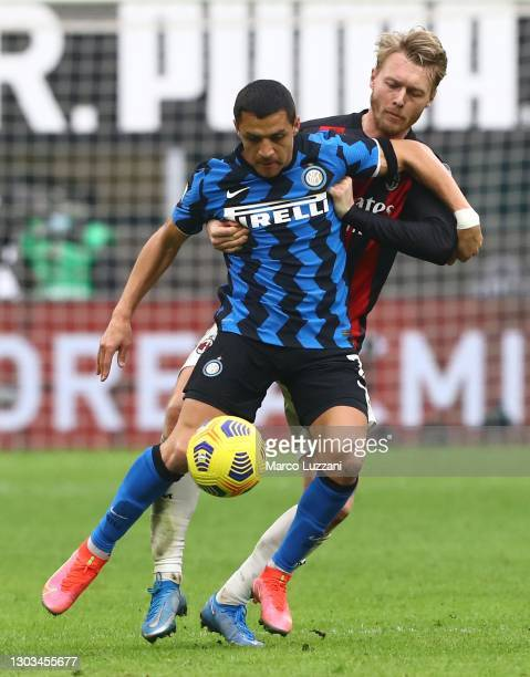Alexis Sanchez of Internazionale competes for the ball with Simon Kjaer of AC Milan during the Serie A match between AC Milan and FC Internazionale...