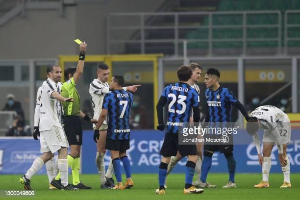 Alexis Sanchez of Internazionale is shown a yellow card by referee Gianpaolo Calvarese for a foul on Federico Chiesa of Juventus during the Coppa...
