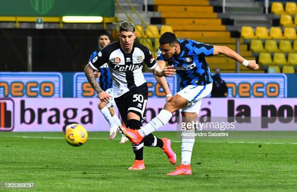 Alexis Sanchez of Internazionale scores his side's first goal whilst under pressure from Lautaro Valenti of Parma Calcio 1913 during the Serie A...