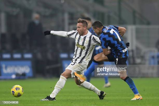 Alexis Sanchez of Internazionale tussles with Arthur of Juventus during the Coppa Italia semi-final match between FC Internazionale and Juventus at...