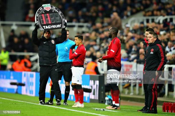 Alexis Sanchez of Manchester United and teammate Romelu Lukaku prepare to come on as substitutes during the Premier League match between Newcastle...