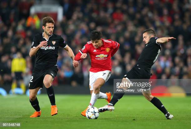 Alexis Sanchez of Manchester United beats Franco Vazquez and Pablo Sarabia of Sevilla FC during the UEFA Champions League Round of 16 Second Leg...