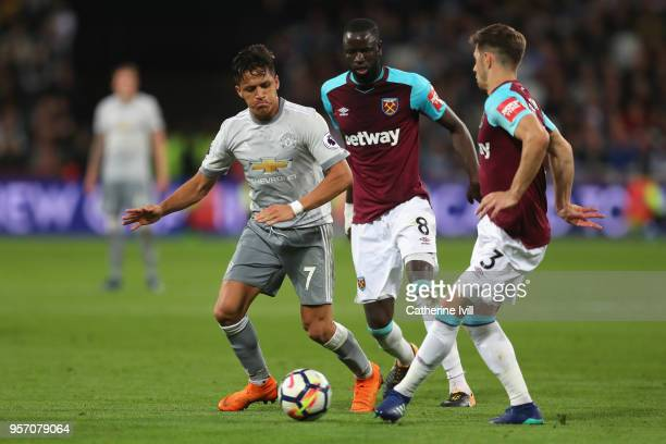 Alexis Sanchez of Manchester United Cheikhou Kouyate and Aaron Cresswell of West Ham United battle for possession during the Premier League match...