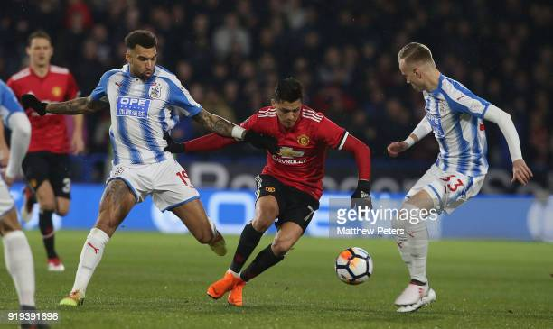 Alexis Sanchez of Manchester United in action with Jordan Williams and Florent Hadergjonaj of Huddersfield Town during the Emirates FA Cup Fifth...