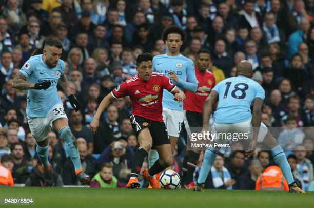 Alexis Sanchez of Manchester United in action with Nicolas Otamendi and Fabian Delph of Manchester City during the Premier League match between...