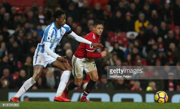 Alexis Sanchez of Manchester United in action with Terence Kongolo of Huddersfield Town during the Premier League match between Manchester United and...