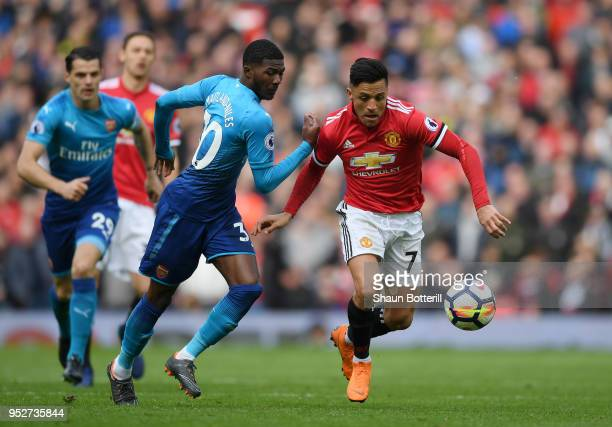 Alexis Sanchez of Manchester United is challenged by Ainsley MaitlandNiles of Arsenal during the Premier League match between Manchester United and...