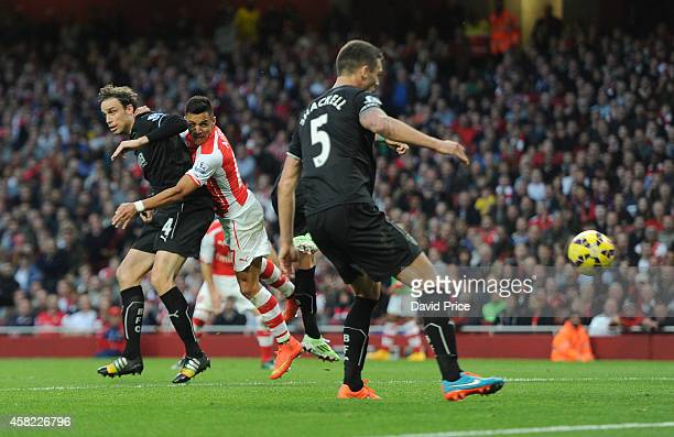 Alexis Sanchez scores Arsenal's 1st goal under pressure from Michael Duff of Burnley during the match between Arsenal and Burnley in the Barclays...