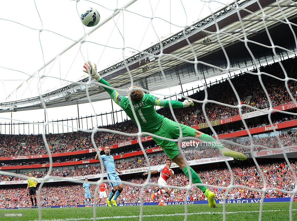 Alexis Sanchez scores Arsenal's 2nd goal past Joe Hart of Manchester City during the Barclays Premier League match between Arsenal and Manchester City at Emirates Stadium on September 13, 2014 in London, England.