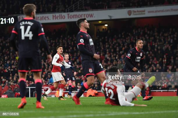 Alexis Sanchez scores Arsenal's 3rd goal during the Premier League match between Arsenal and Huddersfield Town at Emirates Stadium on November 29...