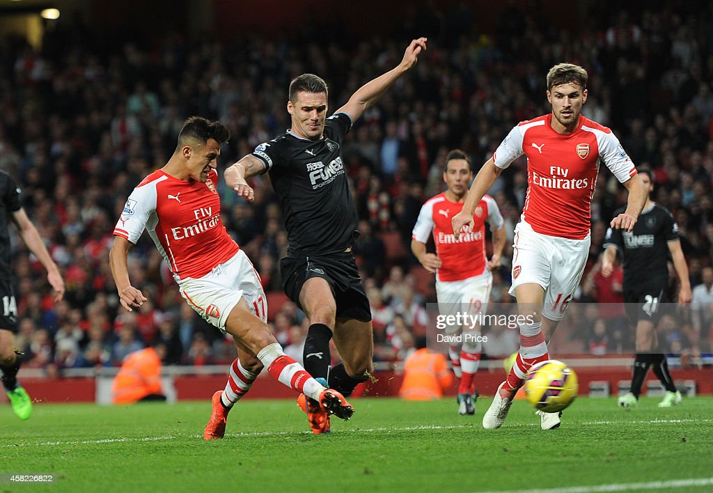 Alexis Sanchez scores Arsenal's 3rd goal, his 2nd, under pressure from Jason Shackell of Burnley during the match between Arsenal and Burnley in the Barclays Premier League at Emirates Stadium on November 1, 2014 in London, England.