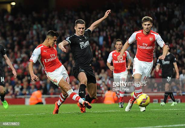 Alexis Sanchez scores Arsenal's 3rd goal his 2nd under pressure from Jason Shackell of Burnley during the match between Arsenal and Burnley in the...