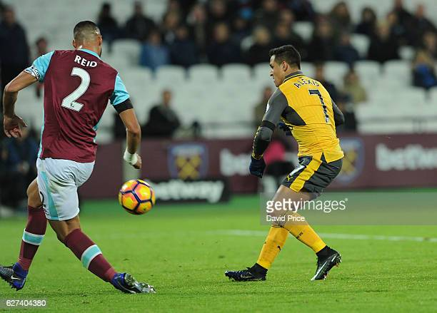 Alexis Sanchez scores Arsenal's 5th goal his 3rd under pressure from Winston Reid of West Ham during the Premier League match between West Ham United...