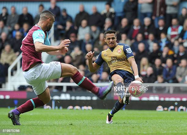 Alexis Sanchez scores Arsenal's second goal under pressure from Winston Reid of West Ham during the Barclays Premier League match between West Ham...