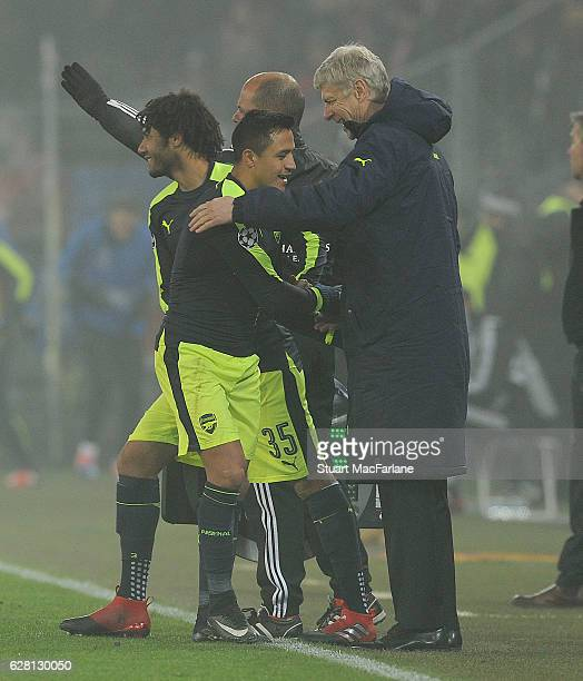 Alexis Sanchez shakes hands with Arsenal manager Arsene Wenger after his substitution during the UEFA Champions League match between FC Basel and...