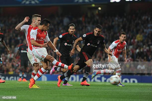 Alexis Sanchez shoots past Besiktas goalkeeper Tolga Zengin to score for Arsenal during the UEFA Champions League Qualifier 2nd leg match between...