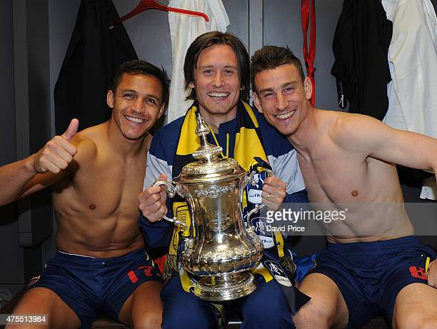 Alexis Sanchez Tomas Rosicky and Laurent Koscielny of Arsenal in the changingroom with the FA Cup Trophy after the match between Arsenal and Aston...
