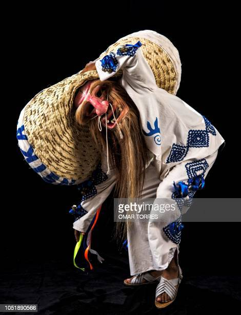 Alexis Santiago Gonzalez Davila poses for a photograph with his traditional costume during the presentation of the Huey Atlixcayotl Festival on...