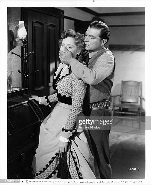 Alexis Smith has her mouth covered by Stephen McNally in a scene from the film 'Wyoming Mail' 1950