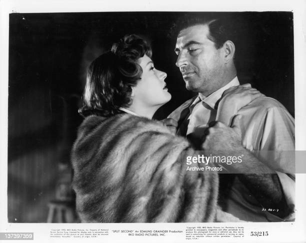 Alexis Smith holding onto Stephen McNally in a scene from the film 'Split Second' 1953