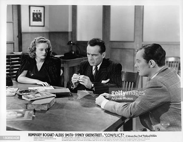 Alexis Smith Humphrey Bogart and unidentified man sitting at table looking at ring in a scene from the film 'Conflict' 1945