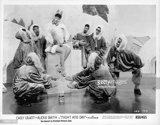 Alexis Smith performs a dance routine surrounded by male dancers in Eskimo costumes in a scene from the film 'Night And Day' 1946