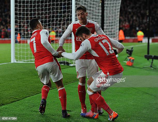 Alexis Snachez and Mesut Ozil help up Olivier Giroud of Arsenal after the 3rd Arsenal goal scored by Alexis Sanchez during the Premier League match...