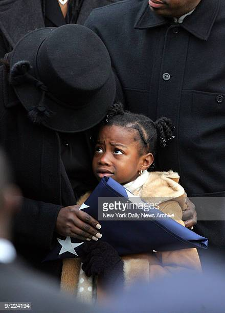 Alexis Stewart holds a flag as she is comforted by her mother Leslyn during funeral services for her father Police Officer Dillon Stewart outside New...