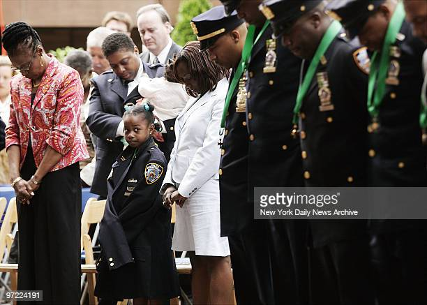 Alexis Stewart wears a police officer's uniform jacket as she stands with her grandmother Winifred baby sister Samantha held by Officer Sharon Brown...