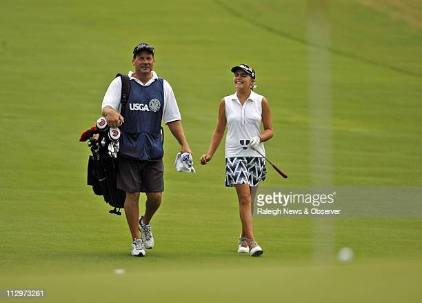 Alexis Thompson right and her father/caddie Scott Thompson enjoy the stroll up 18 during the second round of the US Women's Open at Pine Needles in...