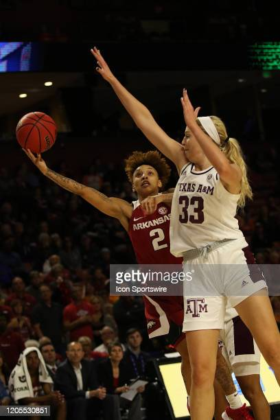 Alexis Tolefree of Arkansas stretches out to take a shot past the defense of Anna Dreimane of Texas AM during the SEC Women's College basketball...
