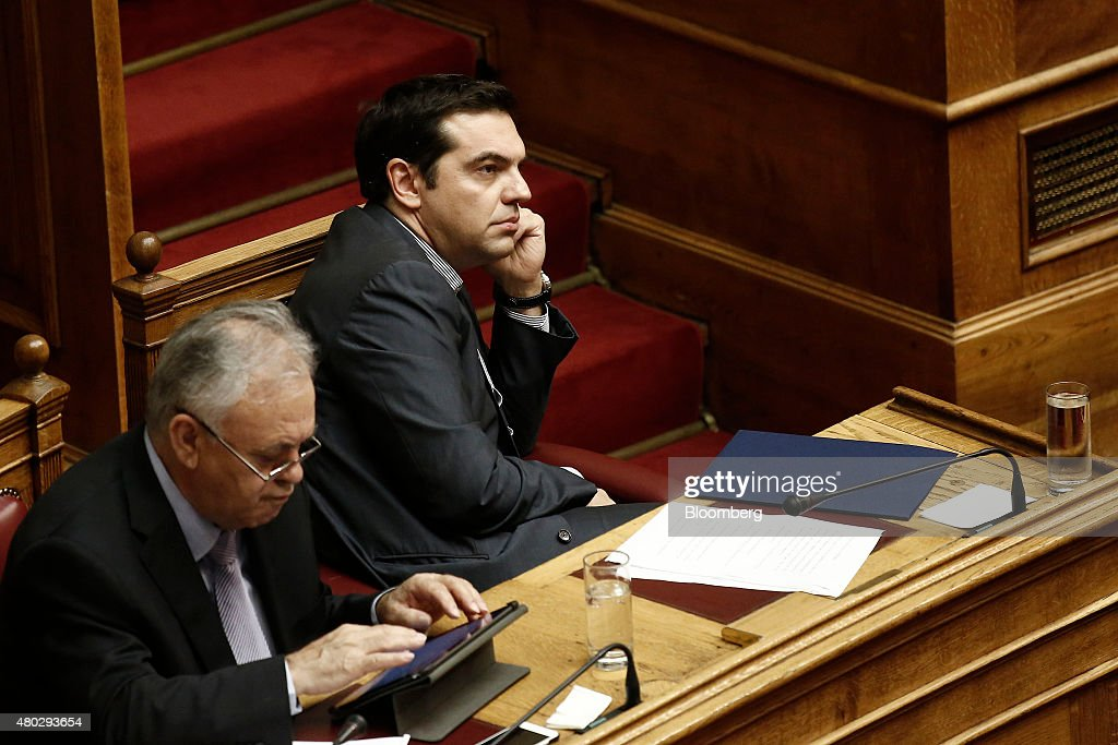 Alexis Tsipras, Greece's prime minister, right, sits and listens at the Greek parliament in Athens, Greece, on Saturday, July 11, 2015. Greek lawmakers debated Prime Minister Alexis Tsiprasâs bailout proposal into the early hours of Saturday before a weekend of political wrangling with creditors on his nationâs place in the euro. Photographer: Kostas Tsironis/Bloomberg via Getty Images