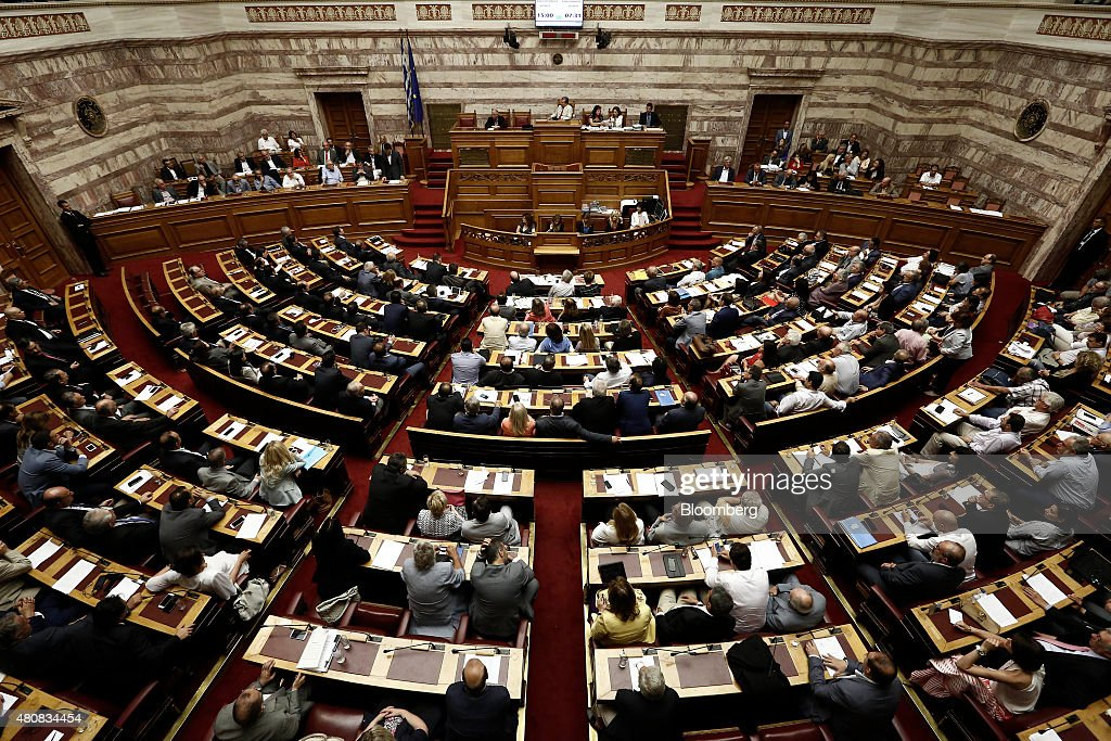 Alexis Tsipras, Greece's prime minister, standing left of center, speaks before a parliamentary vote on whether to accept bailout conditions in Athens, Greece, on Thursday, July 16, 2015. Greek lawmakers passed a bailout agreement that keeps the country in the euro for now, shifting attention to the European Central Bank as it weighs whether to pump more money into the country's hobbled financial system. Photographer: Kostas Tsironis/Bloomberg via Getty Images