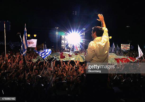 Alexis Tsipras Greece's prime minister waves to supporters during a rally against accepting bailout conditions on Syntagma Square in Athens Greece on...