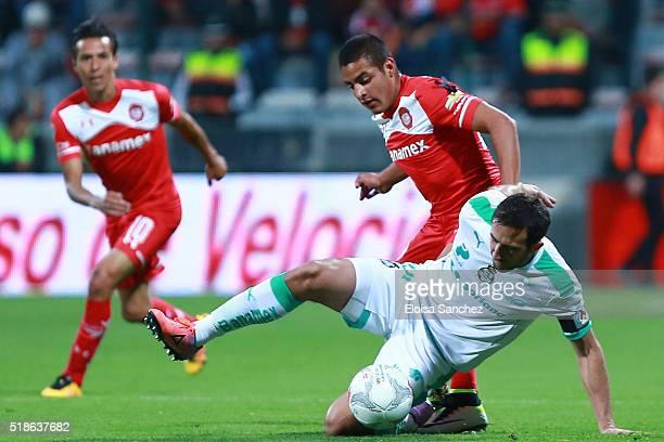 Alexis Vega of Toluca struggles for the ball with Carlos Izquierdoz of Santos Laguna during the 12th round match between Toluca and Santos Laguna as...