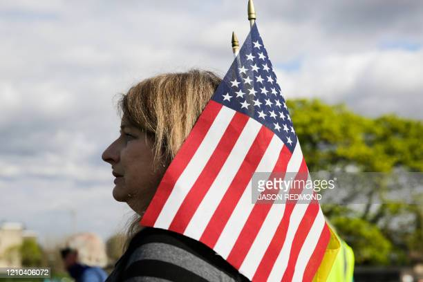 Alexis Wallace of Olympia Washington holds a US flag during a demonstration against Washington state's stayhome order at the state capitol in Olympia...