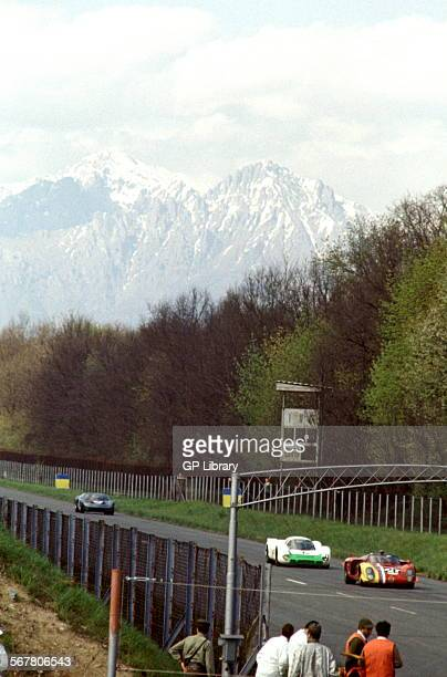 Alfa Romeo leads a Porsche and Ford GT40 in the 1000Kms race at Monza the snow capped Alps in the background 25 April 1969