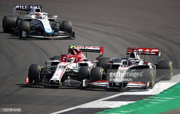 Alfa Romeo's Italian driver Antonio Giovinazzi and Haas F1's French driver Romain Grosjean touch wheels as they race side by side through a corner...