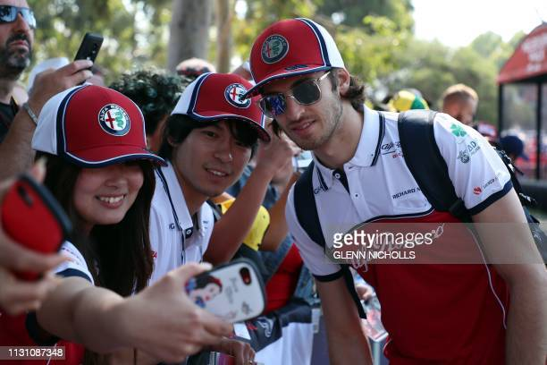 Alfa Romeo's Italian driver Antonio Giovinazzi poses for selfies as he arrives at the circuit in Melbourne on March 17 for the Formula One Australian...