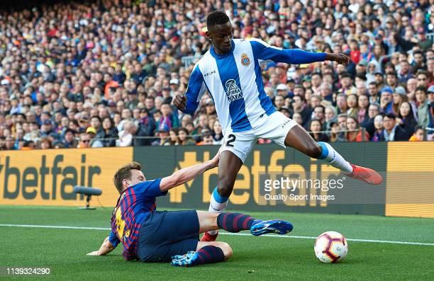 Alfa Semedo of Espanyol is tackled by Ivan Rakitic of Barcelona during the La Liga match between FC Barcelona and RCD Espanyol at Camp Nou on March...