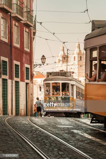 alfama, lisbon. tramway crossroad and cathedral on background. - tram stockfoto's en -beelden