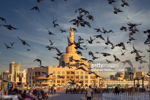 al-fanar qatar islamic cultural center daylight exterior view with pigeons flying in the sky - qatar stock pictures, royalty-free photos & images