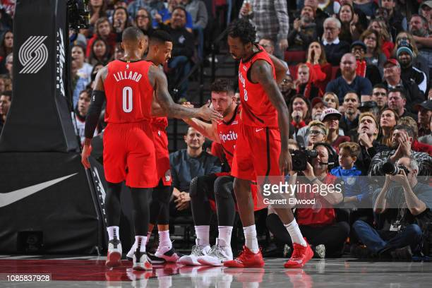 AlFarouq Aminu and CJ McCollum of the Portland Trail Blazers assist Jusuf Nurkic of the Portland Trail Blazers off the floor during the game against...