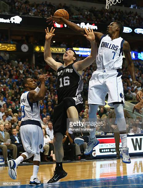 AlFarouq Aminu of the Dallas Mavericks blocks the shot by Aron Baynes of the San Antonio Spurs at American Airlines Center on December 20 2014 in...